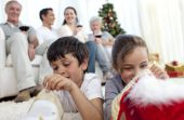 stock photo of christmas party  - Children looking for presents in Christmas boots and family on sofa - JPG