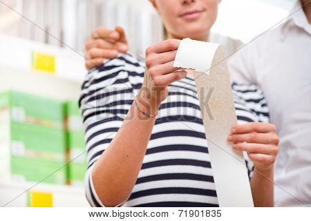 Couple Checking A Long Supermarket Receipt