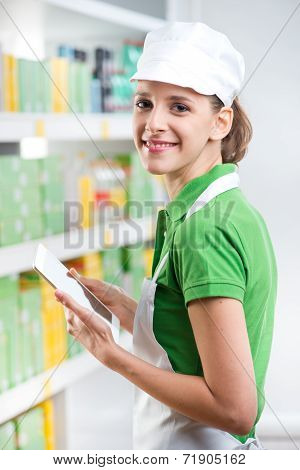 Female Sales Clerk With Tablet At Supermarket