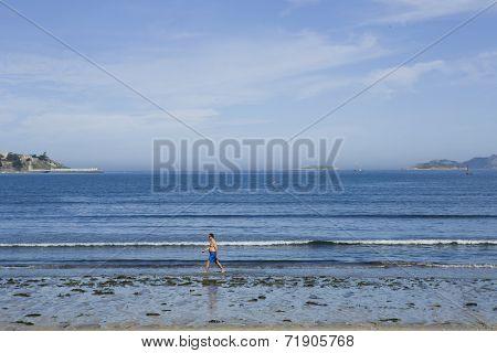 BAIONA, GALICIA, SPAIN - AUGUST 30: Man walking at the beach in the morning, on August 30, 2014 in Baiona, Galicia, Spain.