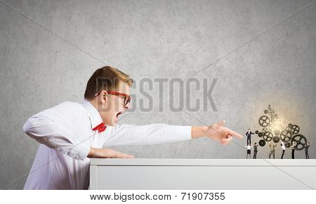 Businessman looking from under the table at businessteam