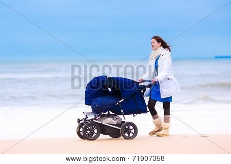 Mother With Twin Stroller On A Beach