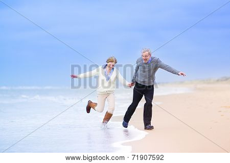 Middle Aged Couple Running On A Beach