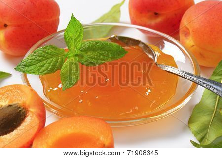 detail of ripe apricots and bowl of apricot jam