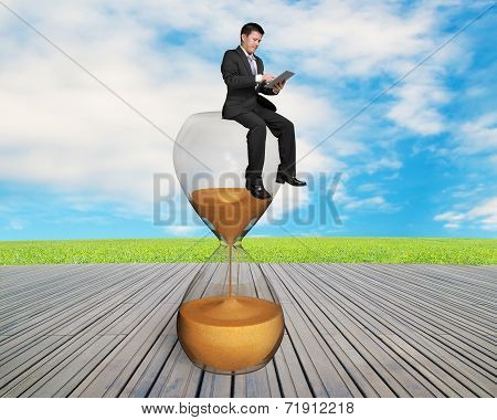 Man Using Smart Pad Sitting On Sandglass
