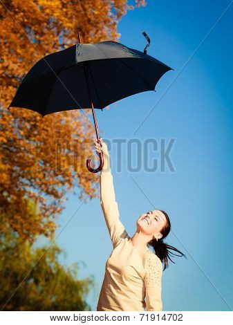 Girl Jumping With Blue Umbrella In Autumnal Park