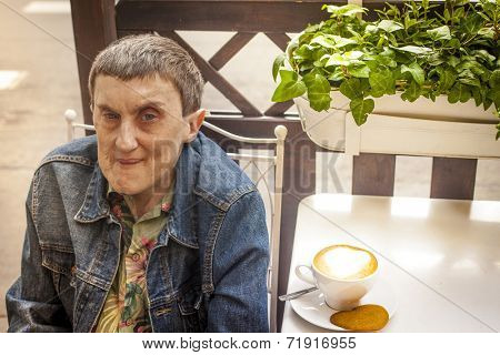 Disabled man with cerebral palsy, smiling sitting at an outdoor cafe.