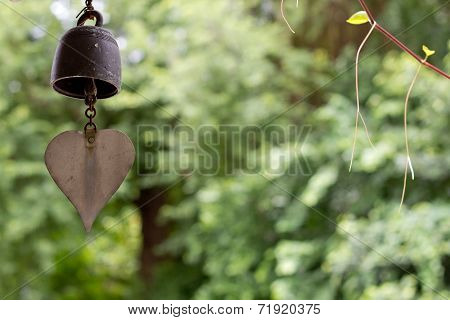 The bell hang on the tree that grow in temple area