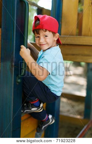 Little Boy In Cap Climb Up