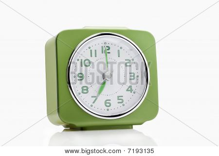 green alarm clock with green arrows and numbers