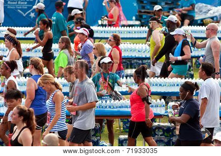Volunteers Hand Out Water Bottles To Exhausted Runners After Race