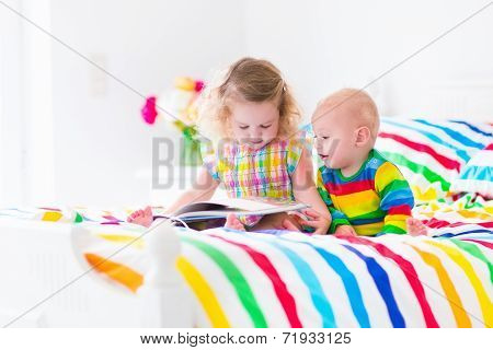 Two Kids Reading A Book In Bed