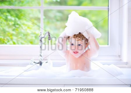 Funny Little Baby Girl Playing With Water And Foam In A Big Kitchen Sink