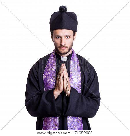 Young catholic priest praying