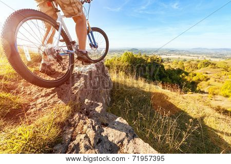 Mountain biker in action on rocks looking at downhill trail against blue sky concept for healthy lifestyle, exercise and extreme sports