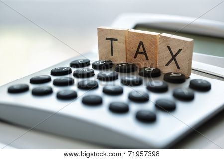 Calculator with the word tax written in wooden block letters