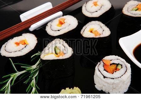 Maki Rolls and California rolls made of fresh raw Salmon, Tuna and Eel with Cream Cheese and Avocado . on black wooden plate . Maki Sushi and Nigiri