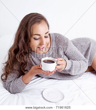 beautiful young brunette woman having a cup of coffee in bed at home