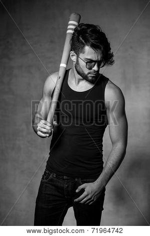 Sexy Fashion Man Model With A Baseball Bat Posing Dramatic Against Grunge Wall