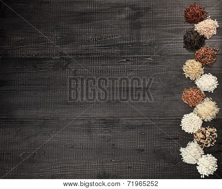 Border Frame made of colorful varieties whole grain rice in a rustic wooden surface background