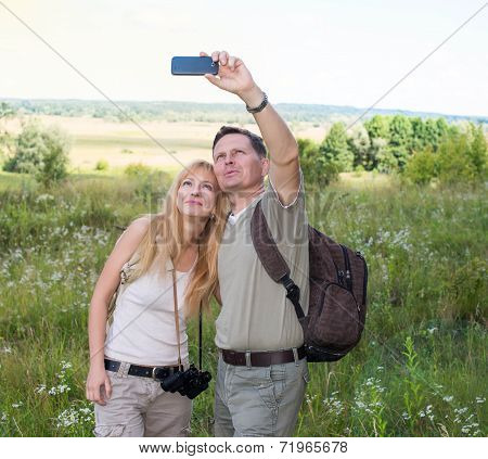 Happy couple taking selfie photo with smart phone hiking in the valley. Woman and man hiker with bac