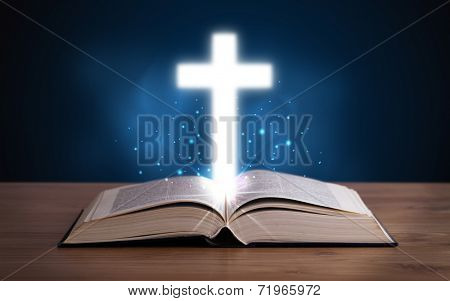 Open holy bible with glowing cross in the middle on wooden deck