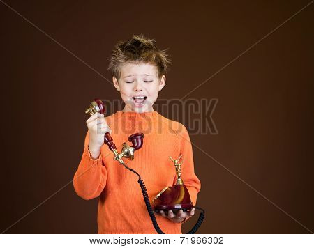 An angry boy screaming in telephone receiver on brown background. Child yelling on a retro phone.