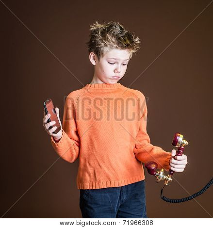 Confused boy holding one red retro rotary telephone in one hand and a cellular phone in the other. C