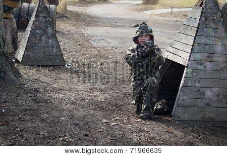 Little boy player with gun during lasertag game.
