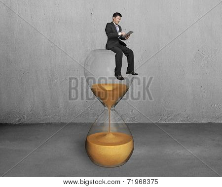 Man Use Tablet And Sit On Hourglass