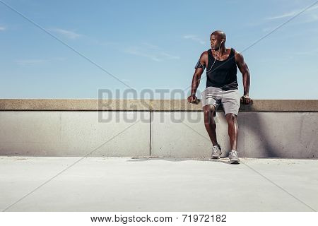Male Runner Relaxing On Embankment Looking Away Copyspace
