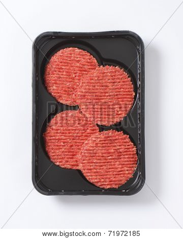 four raw hamburger patties on black plastic tray