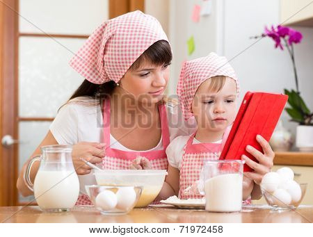 Mother And Child Preparing Pastry Together At Kitchen And Looking At Tablet For Receipe