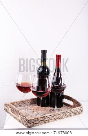Glasses and wine bottle on tray in room