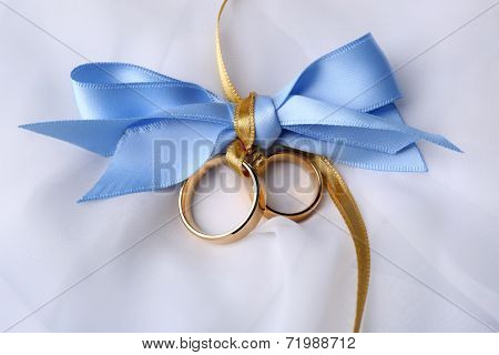 Wedding rings tied with ribbon on light background
