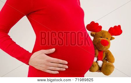 Close up on pregnant belly, dressed in red.