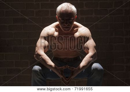 Muscular Man Sitting In Spotlight