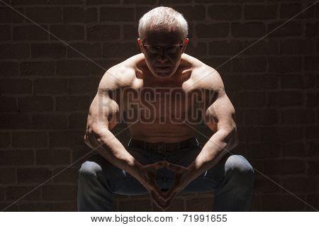 Muscular Man Sitting In Spotlight