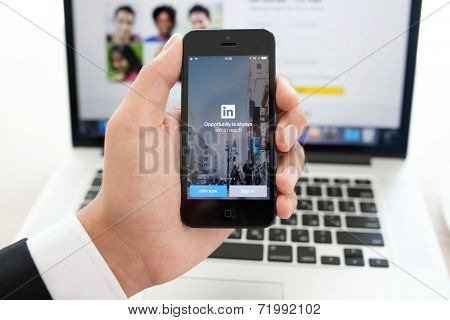 Businessman Holding Iphone 5S With App Linkedin On The Screen On A Background Of Macbook Pro