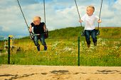 stock photo of swing  - Little blonde boys having fun at the playground - JPG