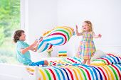 image of pillow-fight  - Two children happy laughing boy and cute curly little girl having fun at pillow fight with feathers in the air jumping laughing and giggling in a white bedroom with colorful bedding - JPG