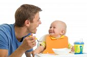 foto of child feeding  - cute father feeding baby son isolated on white - JPG