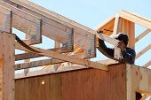 stock photo of rafters  - Construction framing contractor installing the roof truss system to a new commercial residential development - JPG