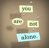 image of bulletin board  - You Are Not Alone words on paper pinned to a bulletin board assuring you you - JPG