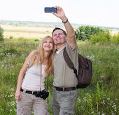 picture of two women taking cell phone  - Happy couple taking selfie photo with smart phone hiking in the valley - JPG