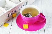 foto of tea bag  - Cup with tea and tea bags on wooden table close - JPG
