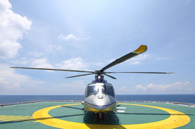 picture of helicopters  - helicopter parking landing on offshore platform. Helicopter transfer crews or passenger to work in offshore oil and gas industry.