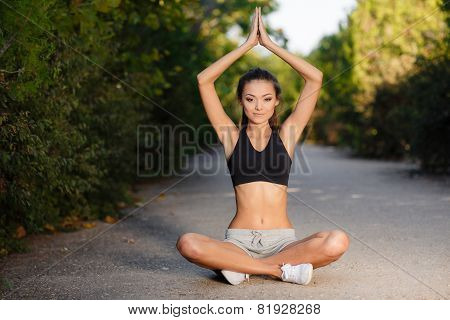 Young woman meditating peacefully in the park in the summer.