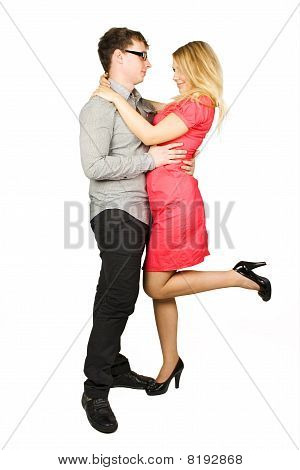 Young Man In Glasses And Blond Girl In Red Dress Standing And Embracing Isolated On White, Side View