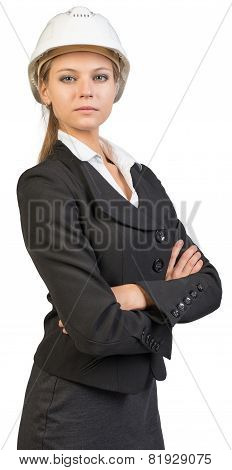 Businesswoman wearing hard hat, her arms crossed on breast